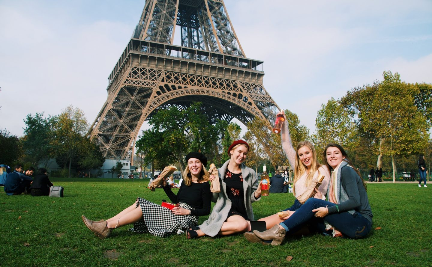 Enjoying a picnic in front of the Eiffel Tower with wine and cheese!