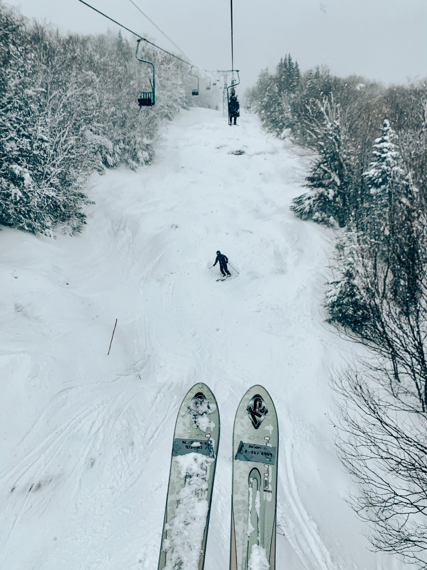 Photo of skis from chairlift looking down at trail