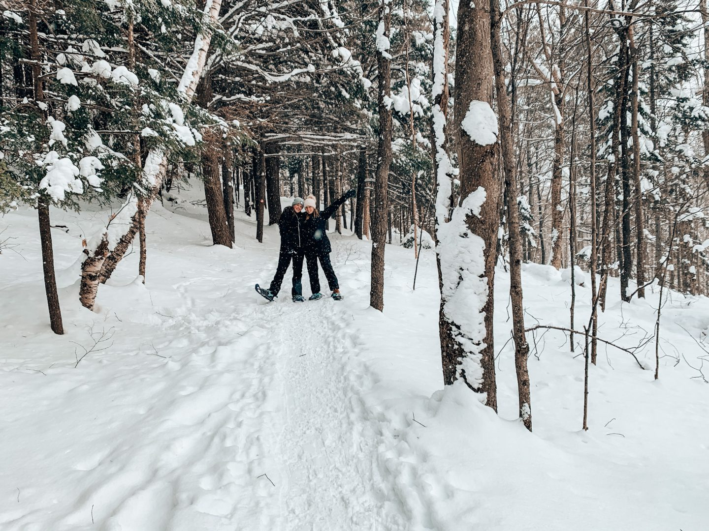 Two girls pose on snowy path in between trees