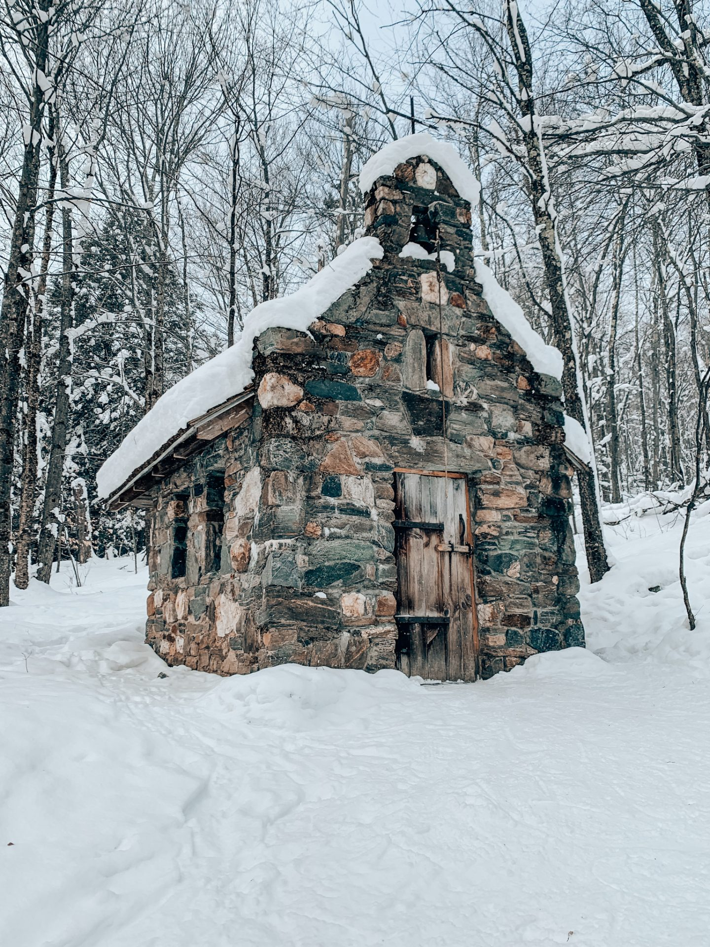 Photo of snowy chapel made of stone