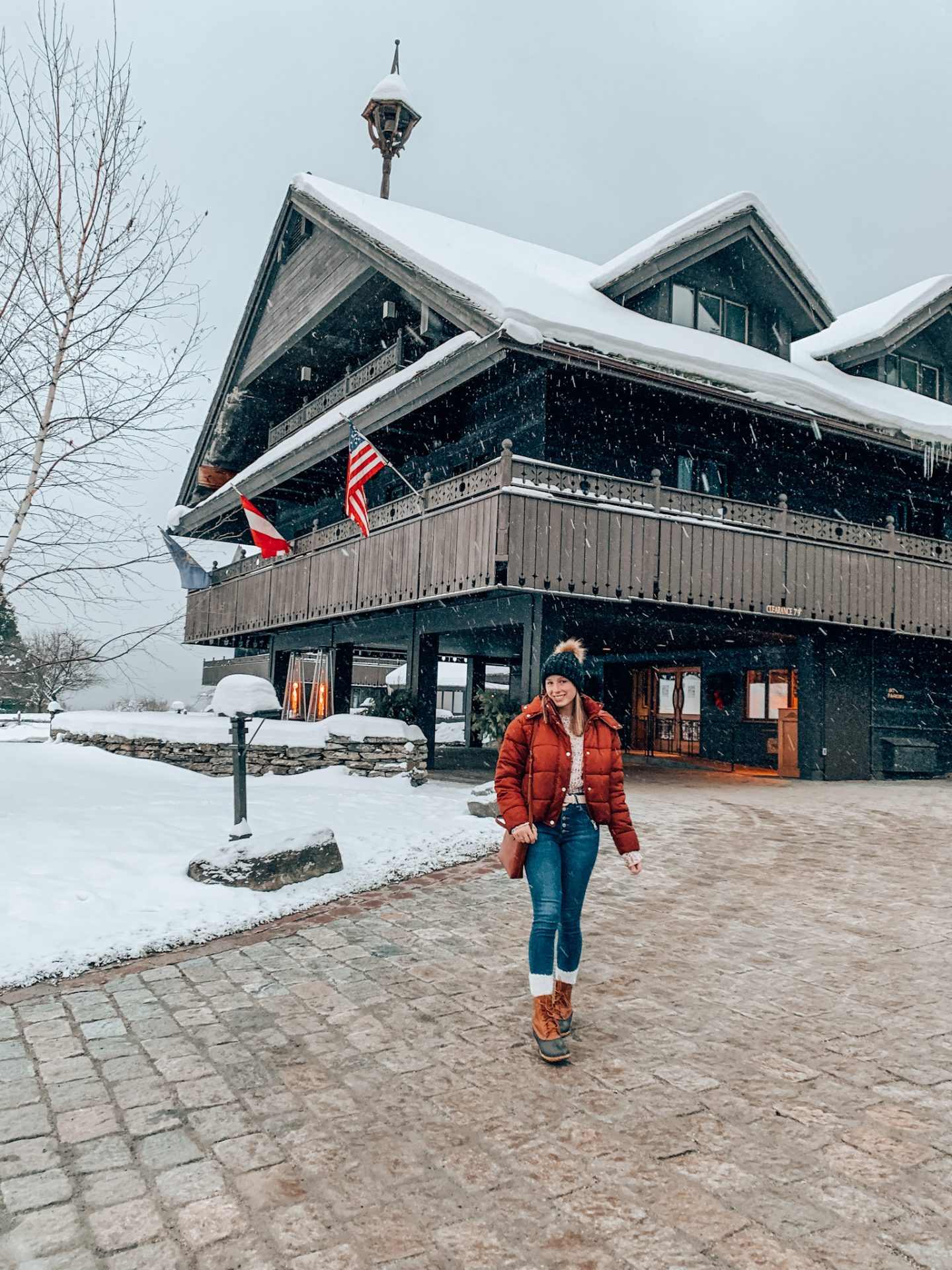 Girl poses in front of the Von Trapp Family Lodge in Stowe, VT in winter weekend