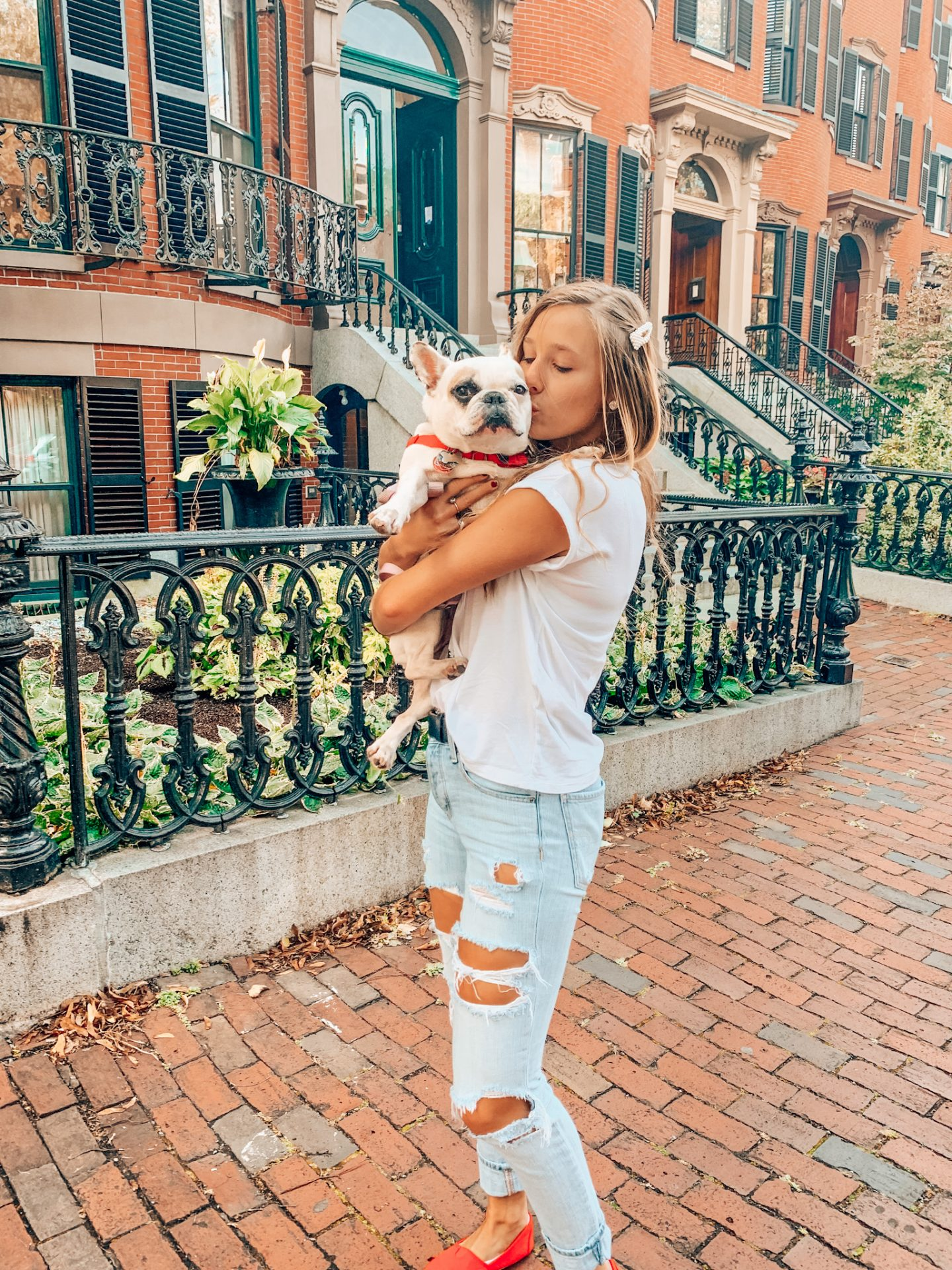 Girl holds french bulldog while posing for Instagram photo in Boston's South End Union Park